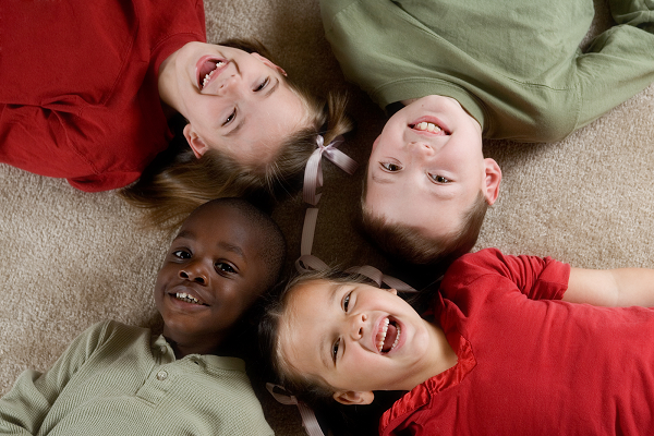 4 children laugh and lay on a carpet. They have their heads together and their bodies pointing in different directions, like forming an X.